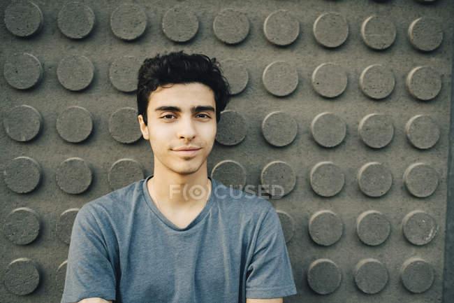 Retrato de un joven confiado de pie contra la pared - foto de stock