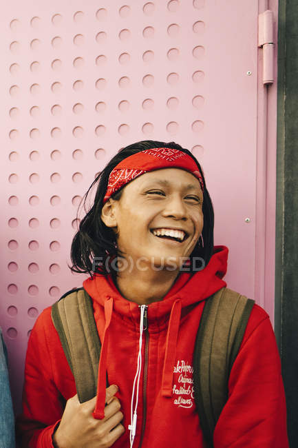Cheerful young man looking away against wall — Stock Photo