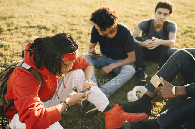High angle view of friends using mobile phones while sitting on field — Stock Photo
