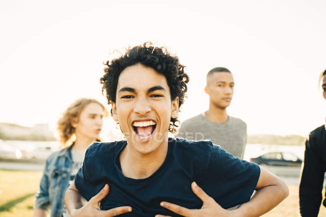 Portrait of happy teenage boy with hands on chest against friends in city — Stock Photo