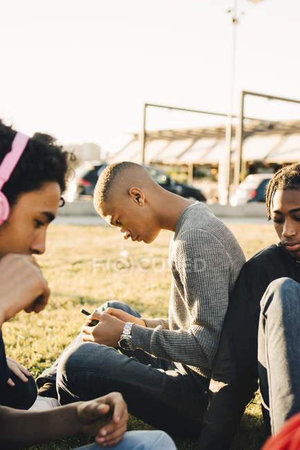 Männliche Freunde sitzen auf Feld an sonnigen Tag — Stockfoto