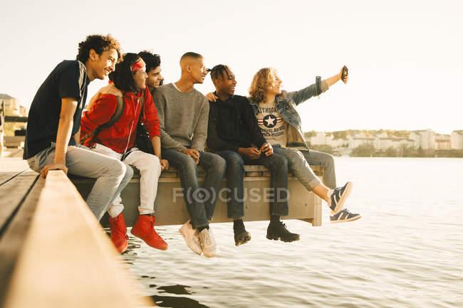 Feliz macho amigos tomando selfie mientras sentado lado a lado en muelle por río - foto de stock