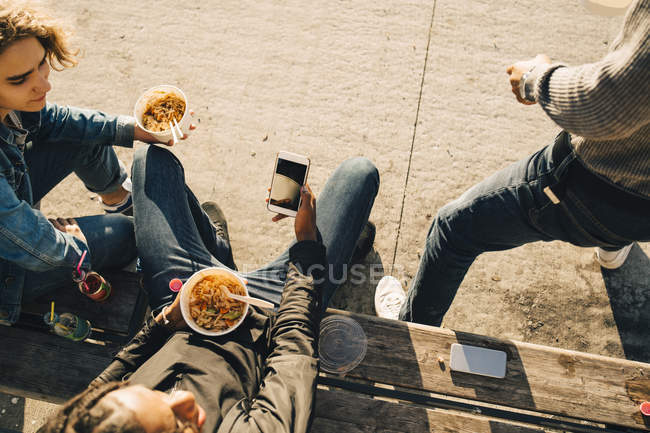High angle view of teenage boy using smart phone while eating meal with friends on street in city — Stock Photo