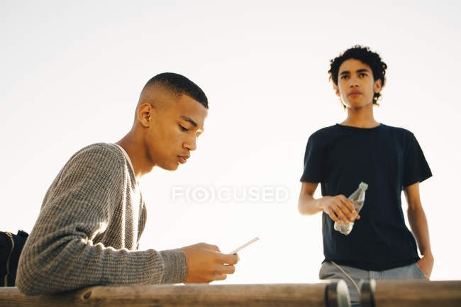 Teenage boy using mobile phone while friend holding water bottle against clear sky during sunny day — Fotografia de Stock