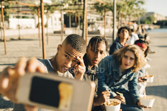 Male friends taking selfie while eating take out food on street in city — Stock Photo