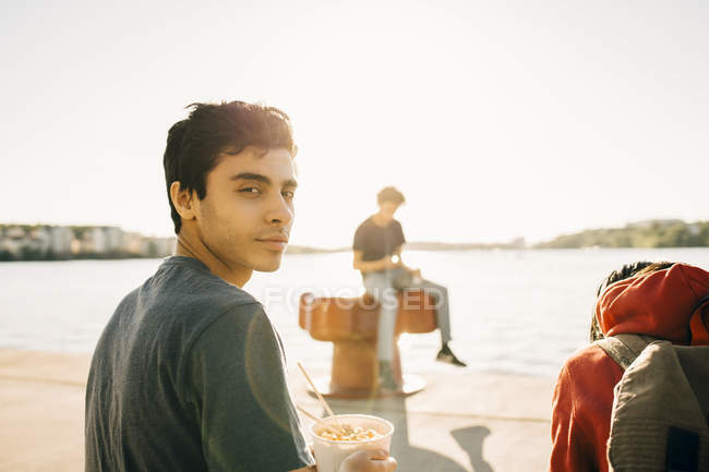 Portrait of young man holding meal in container while sitting on promenade during sunny day — Fotografia de Stock