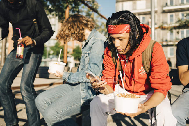 Young man using mobile phone while having take out food by friends in city — Fotografia de Stock