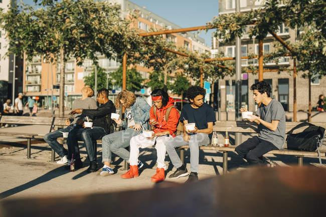 Amigos varones comiendo sacan comida mientras están sentados uno al lado del otro en el banco de la ciudad - foto de stock