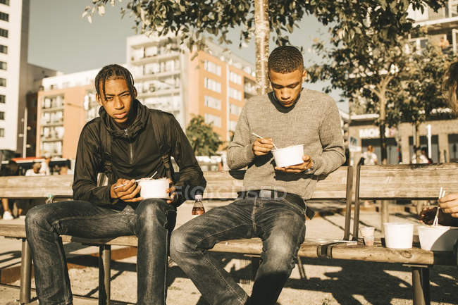 Portrait of serious teenage boy holding take out food while sitting by friend on bench in city during sunny day — Stock Photo
