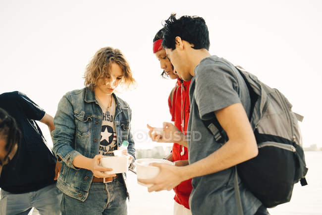 Friends holding take out food while standing on promenade in city during sunny day — Stock Photo