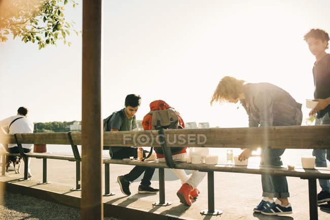 Friends with take out food on promenade in city during sunny day — Stock Photo