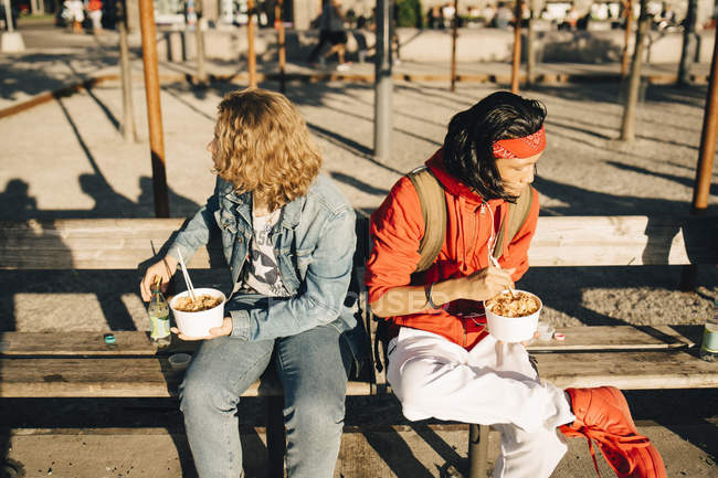 Friends eating take out food while sitting on bench in city during sunny day — Stock Photo