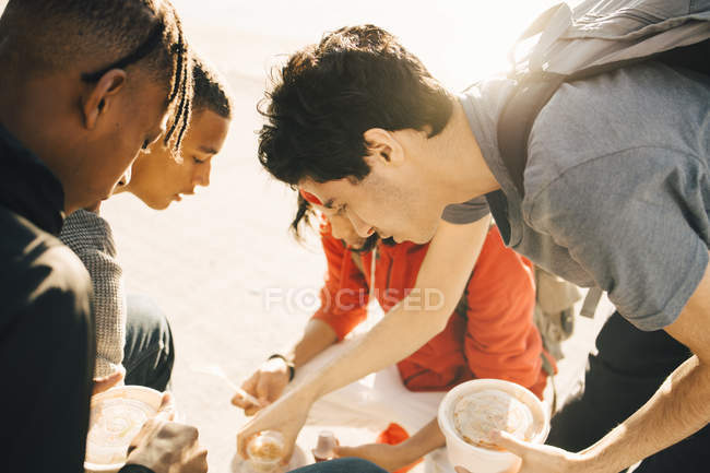 Friends eating take out food on promenade in city during sunny day — Photo de stock