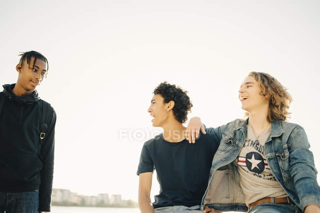 Happy male friends spending leisure time against clear sky in city — Stock Photo
