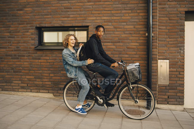 Portrait of teenage boy riding bicycle with friend on street in city — Stock Photo