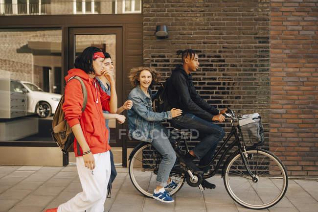 Fröhlicher junger Mann schaut Freunde beim Fahrradfahren in der Stadt an — Stockfoto