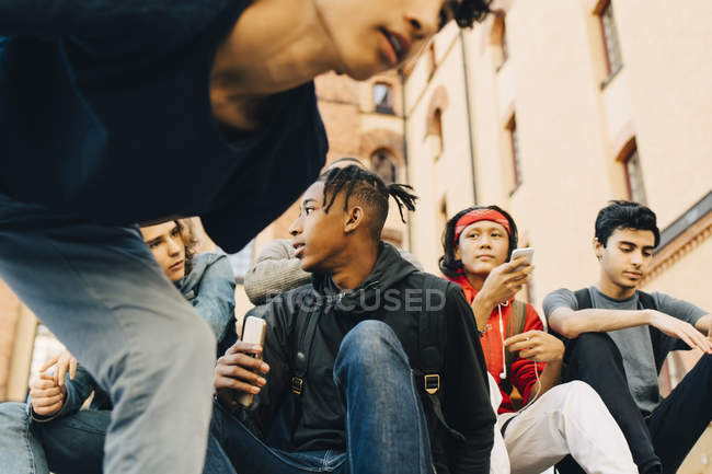 Male friends with mobile phones sitting in city — Stock Photo