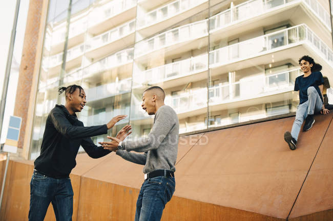 Happy friends greeting while standing in city — Stock Photo