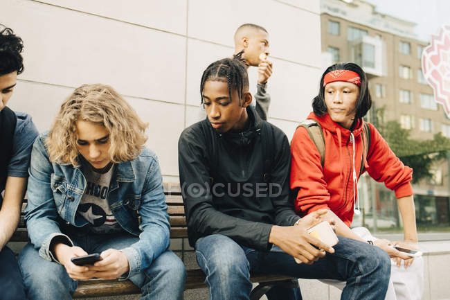 Young man using mobile phone while sitting by friends on bench at sidewalk — Fotografia de Stock