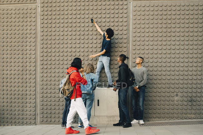 Full length of male friends taking selfie with mobile phone while standing by wall in city — Stock Photo