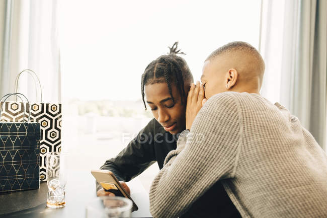 Teenage boy whispering into friend's ear while sitting in restaurant — Fotografia de Stock