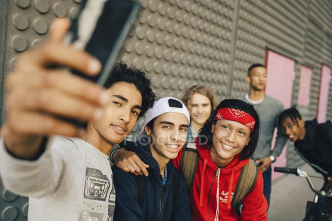 Felices amigos varones tomando selfie con teléfono inteligente en la ciudad - foto de stock
