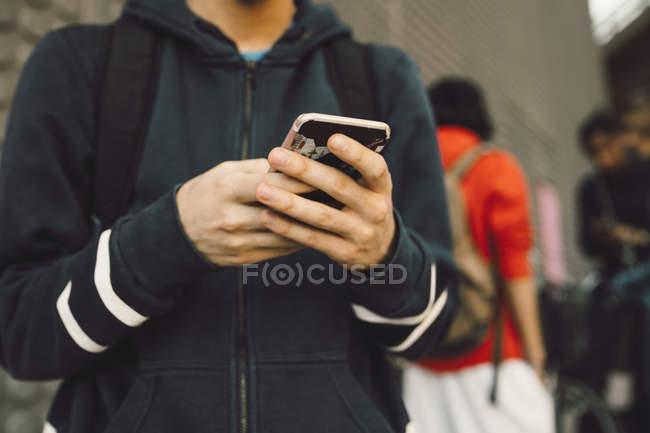 Midsection de hombre joven utilizando el teléfono móvil con amigos en segundo plano en el sendero - foto de stock
