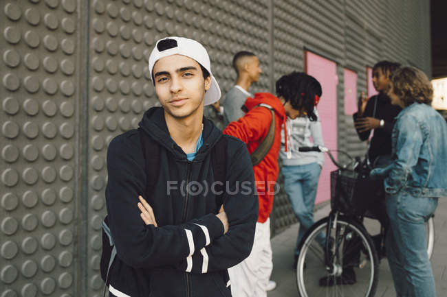 Portrait of confident young man with friends talking in background on footpath — Stock Photo