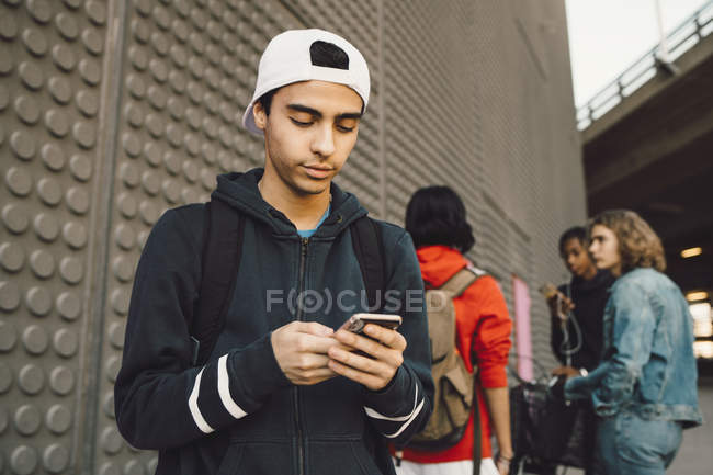 Young man using mobile phone with friends standing in background on footpath — Stock Photo