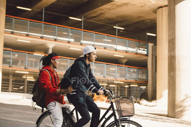 Side view of young man riding bicycle with friend in city — Stock Photo