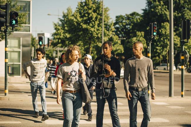 Masculino amigos cruzando estrada na cidade — Fotografia de Stock
