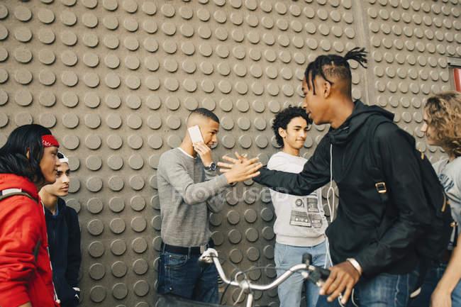 Hombres estrechando las manos mientras están de pie por amigos contra la pared - foto de stock