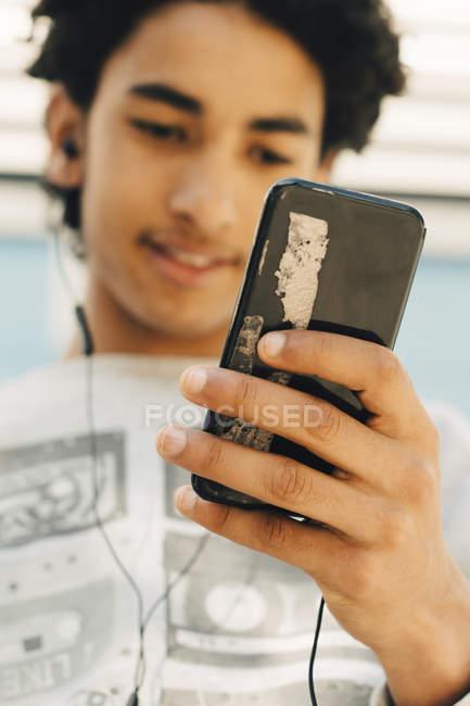 Adolescente usando teléfono móvil en la ciudad - foto de stock