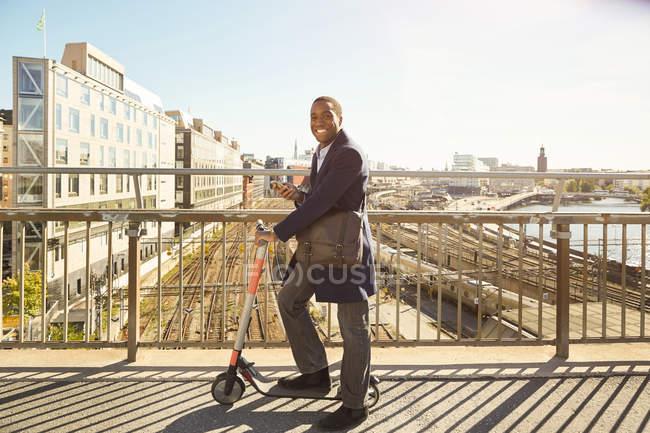 Retrato de vista lateral del joven sonriente de pie con scooter eléctrico en puente en la ciudad - foto de stock