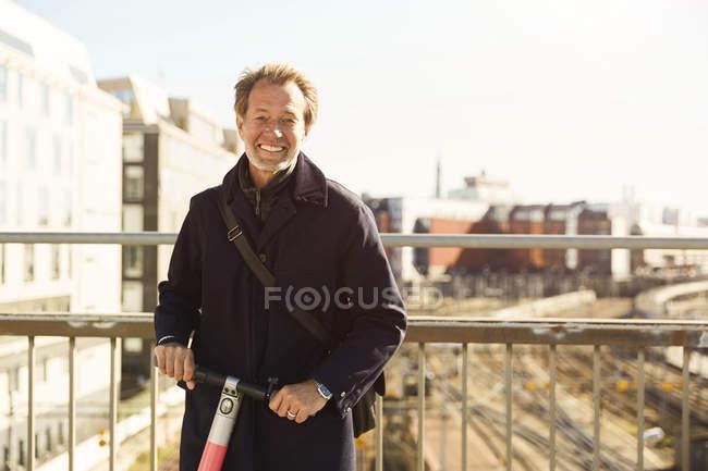 Портрет улыбающегося взрослого мужчины, стоящего с электрическим толкателем на мосту против неба в городе — стоковое фото