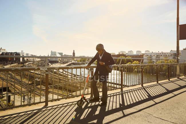 Comprimento total do jovem de pé com scooter elétrico empurrando por trilhos na ponte na cidade — Fotografia de Stock