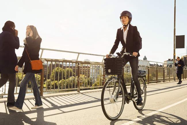 Mulher madura andando de bicicleta elétrica por viajantes na ponte na cidade contra o céu — Fotografia de Stock