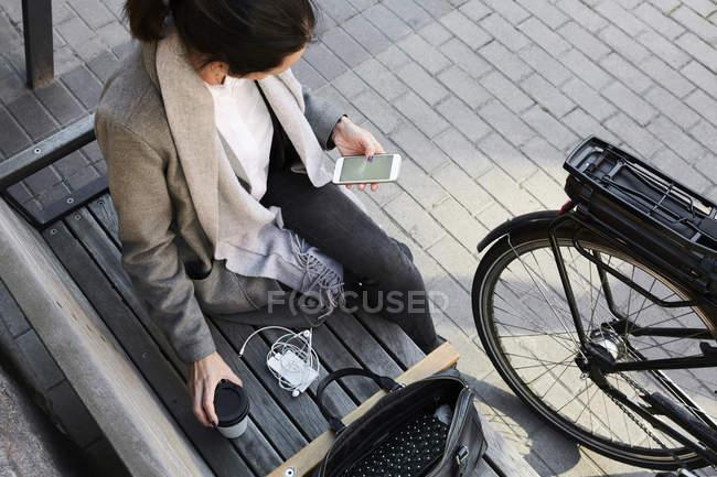 Vista de ángulo alto de la mujer navegando por la red a través del teléfono móvil mientras está sentado en el banco de la ciudad - foto de stock