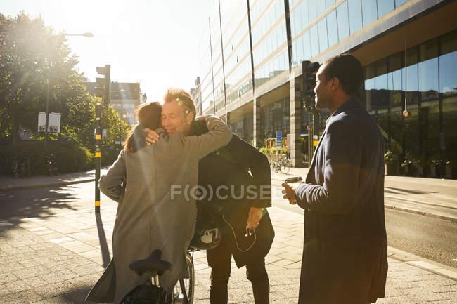 Joven mirando a amigos abrazándose en la acera de la ciudad - foto de stock