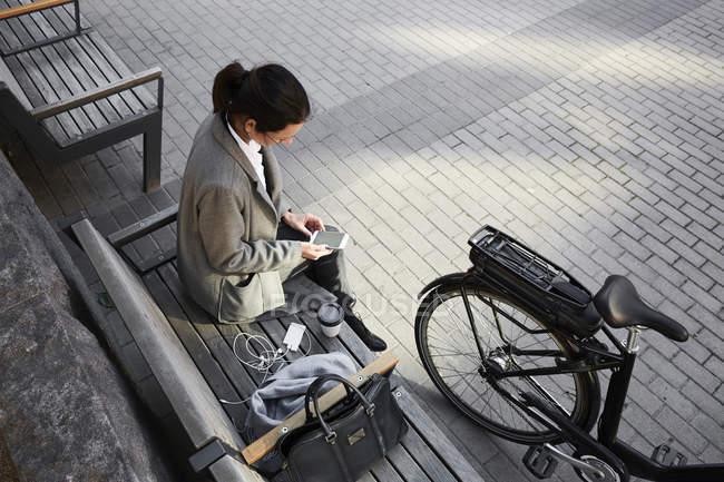 Vista de ángulo alto de la mujer navegando por la red a través del teléfono inteligente mientras está sentado en el banco de la ciudad - foto de stock