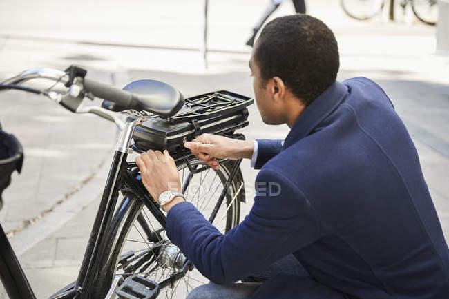 Молодой мужчина пригородных блокировки Электрический велосипед в городе — стоковое фото