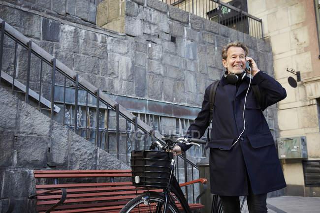 Sorrindo homem falando no telefone inteligente por bicicleta elétrica contra a construção — Fotografia de Stock