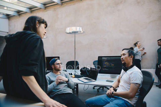 Multi-ethnic computer programmers discussing plan in creative office — Stock Photo