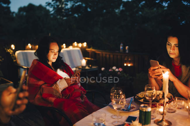 Female friends using mobile phones at table during dining party — Stock Photo