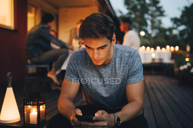 Young man using smart phone while friends in background during dinner party — Stock Photo