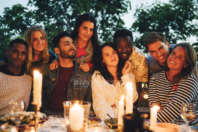 Portrait of happy multi-ethnic male and female friends enjoying dinner party — Stock Photo
