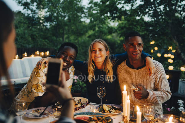 Woman photographing happy male and female friends sitting at table during dinner party — Stock Photo