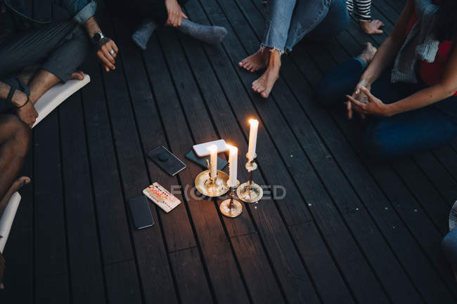 High angle view of friends sitting around lit candles and mobile phones in balcony during group therapy session — Photo de stock