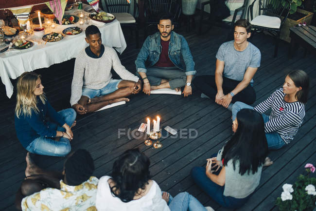 Multi-ethnic male and female friends sitting with eyes closed around lit candles and mobile phones in balcony - foto de stock