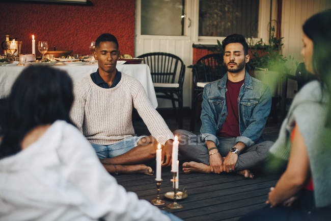 Multi-ethnic male and female friends sitting with eyes closed in balcony during group session - foto de stock